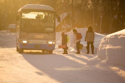 Kids getting on the bus at sunrise in snowy Niseko, Japan.