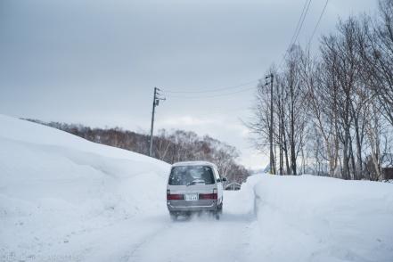 Van driving down a snowy road in Niseko, Japan.