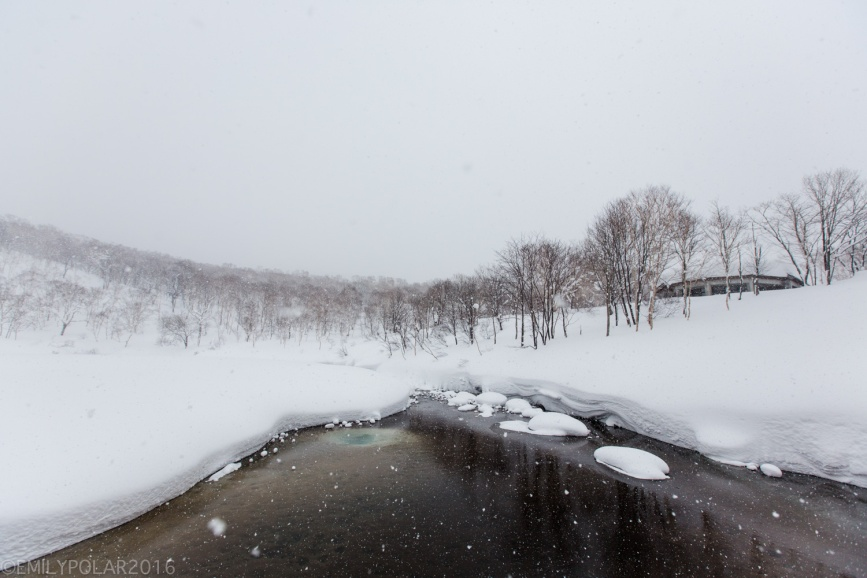 Dark water onsen with snow falling over drifts of powder in the forest of Chise Onsen in Niseko, Japan.