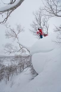 Snowboarder standing on top of huge snow pillow at Chisenupuri in Niseko, Japan.