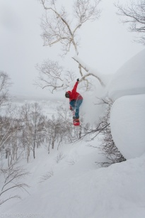 Snowboarder jumping off pillow puff in the backcountry at Chisenupuri in Niseko, Japan.