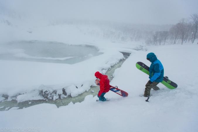 Snowboarders walking along onsen stream at Chise mountain in Niseko, Japan.