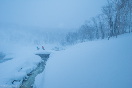 Snowboarders walking on snow bridge over onsen stream at Chise mountain in Niseko, Japan.