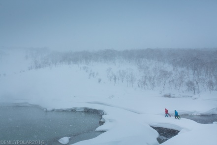 Snowboarders walking on snow bridge over onsen stream at Chise mountain in Niseko, Japan.