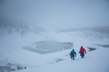 Snowboarders hiking out of the backcountry at Chise along onsen stream in Niseko, Japan.