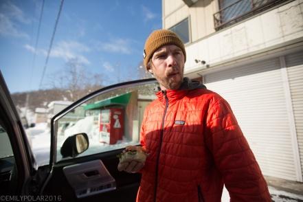 Snowboarder eating a breakfast sandwich en route to snowboarding in Niseko, Japan.