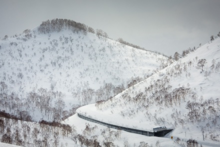 Road tunnel curves around the base of a snowy mountain in the rolling hills of Niseko Japan in the winter.