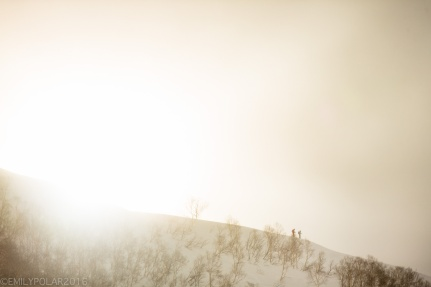 Skiers line up on ridge spotting their lines while the clouds swirl around in Niseko, Japan.