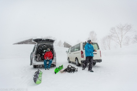 Snowboarders taking a lunch break at the van in the dumping snow at the base of Goshiki in Niseko, Japan.
