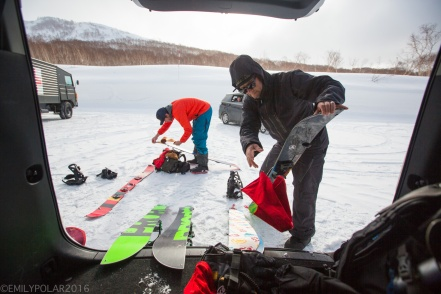 Snowboarders getting their boards ready in the parking lot for a day riding the powder in the backcountry of Niseko, Japan.