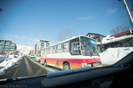 Shuttle bus in Hirafu with red and orange stripes drives down the road out of Hirafu.