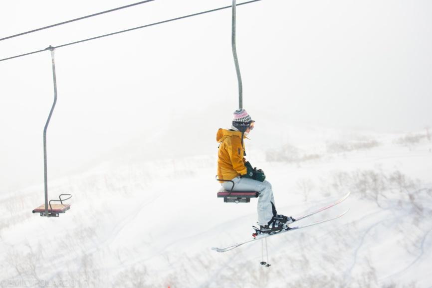 Woman skier sitting on single chair lift up to the top of Hirafu, Niseko, Japan.