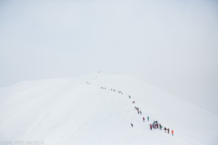 Line of skiers and snowboarders hiking on the summit ridge of Hirafu in a stormy white out.