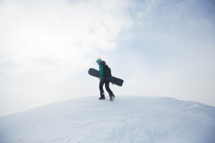 Woman walking up snowy ridge with snowboard in a sunny whiteout at Hirafu, Japan.