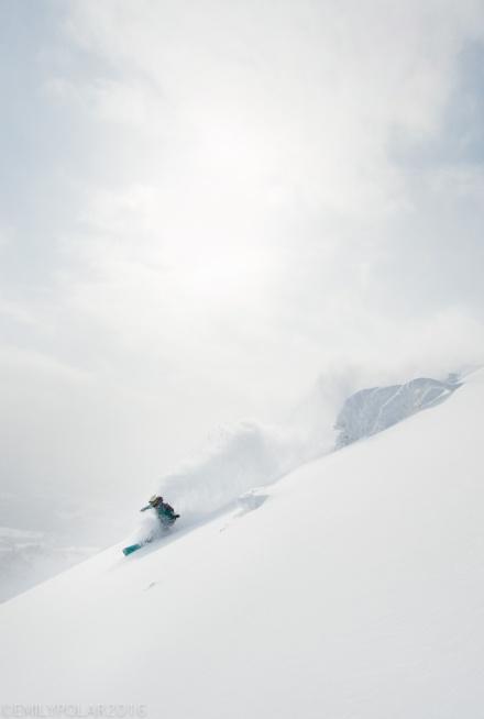 Japanese woman snowboarder slashing some fresh powder at Hirafu Resort in Niseko, Japan.