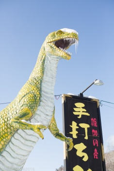 Dinosaur statue in the middle of no where along the roadside in snowy Hokkaido, Japan.