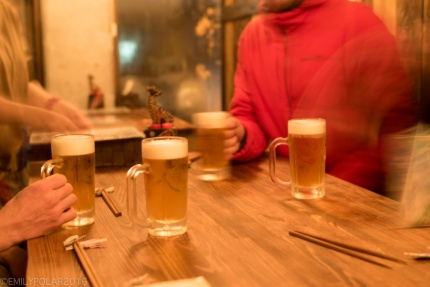 Friends drinking beer and waiting for ramen at Kobito Restaurant in Niseko, Japan.
