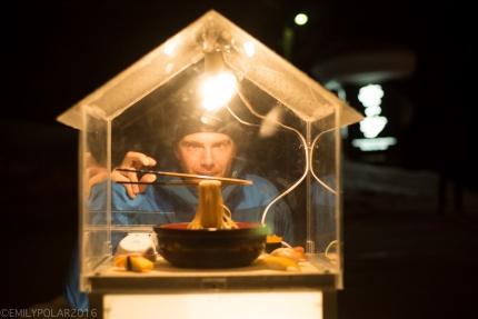 Man standing behind lit up plastic ramen display box acting like he's holding chopsticks at Kobito Restaurant in Niseko, Japan.