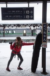 Woman photographer taking pictures with the Lowepro Whistler camera bag at the Kutchan train station in Niseko, Japan.