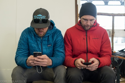 Snowboarders playing on their phones while waiting at the Kuchan train station for the bus to Niseko.