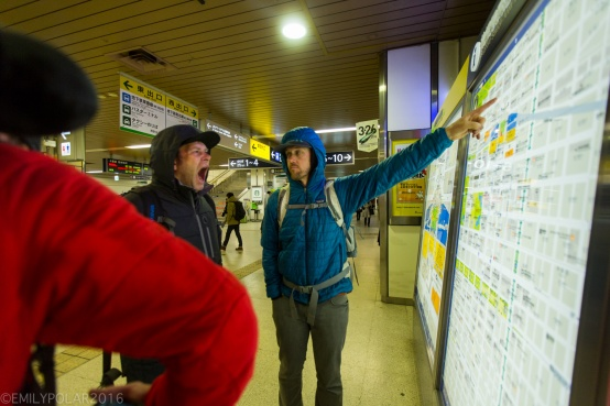 Boys on snowboard trip in Japan tired after traveling look at map in train station to find their way to Niseko.