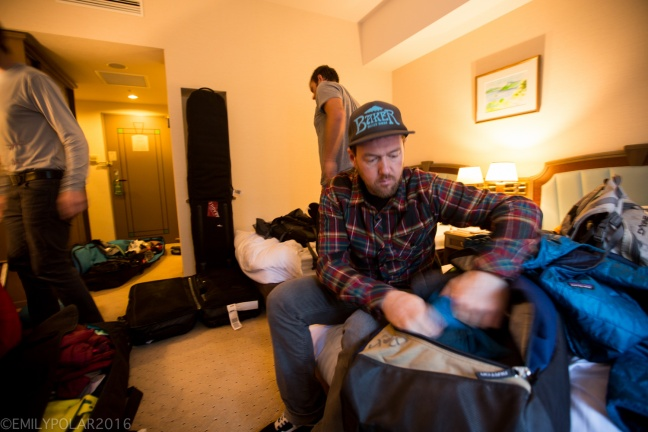 Snowboarders packing gear up in hotel room preparing for a snowboard trip in Niseko, Japan.