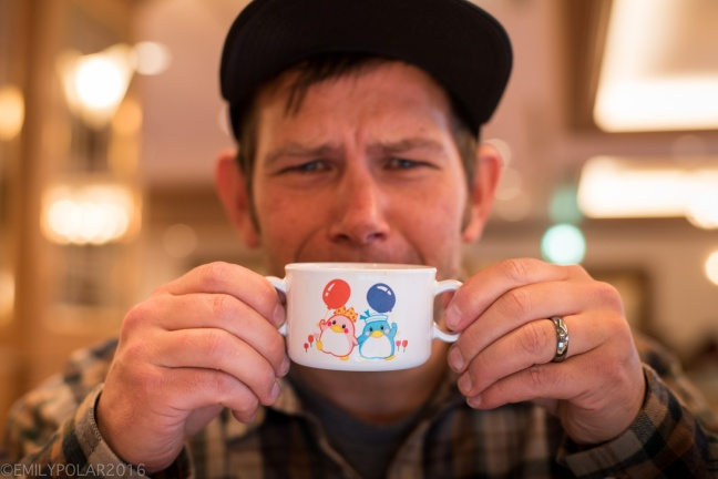 Snowboarder goofing around with kids size cup full of coffee at hotel in Sapporo, Japan.