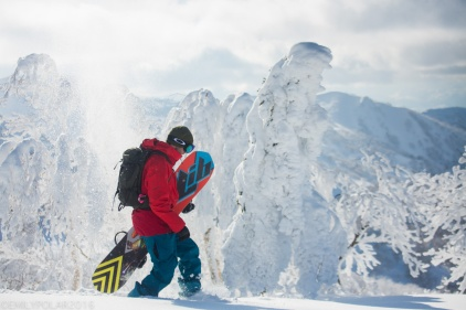 Snowboarder hiking in the snowy backcountry of Kiroro Resort in Japan.