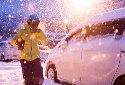 Woman in snowboard gear sipping a warm beverage in the dumping snow of the parking lot at Kiroro in Japan.