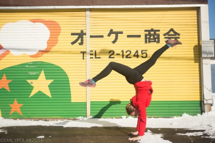 Woman doing a handstand in front of painted garage door in NIseko, Japan.