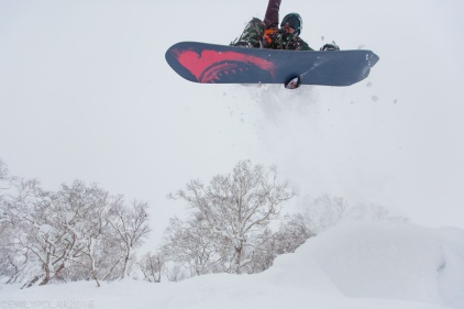 Snowboarders jumping off big pillow in the deep powder snow of Niseko, Japan.