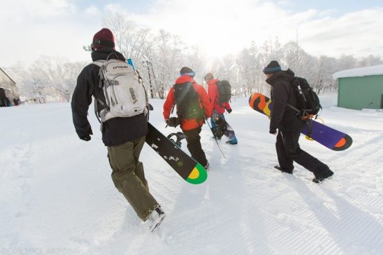 Snowboarders walking with their snowboards in the morning light to first chair at Moiwa in Niseko, Japan.