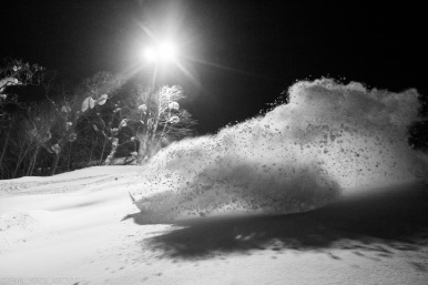 Snowboarders riding in the snow at night at Hirafu Resort in Niseko, Japan.