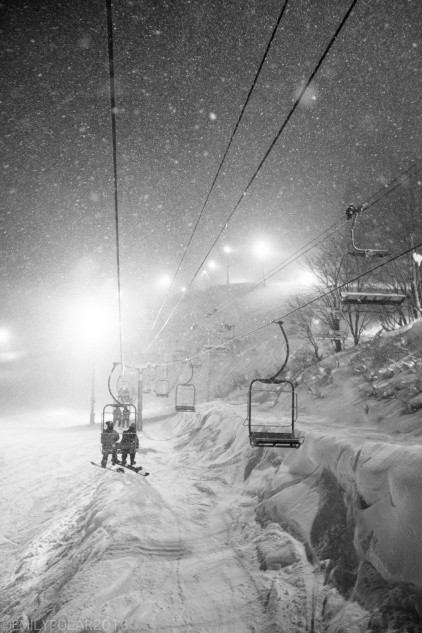 Snowboarders getting on the chair lift at night at Hirafu Resort in Niseko, Japan.