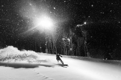 Snowboarders riding in the snow at night at Hirafu Resort in Niseko, Japan.