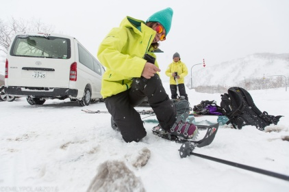 Woman snowboarder getting her snowshoes on and her pack ready for backcountry snowboarding in Nimmi at Hokkaido, Japan.