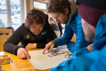 Men looking at map for backcountry snowboarding in the mountains surrounding Niseko, Japan.