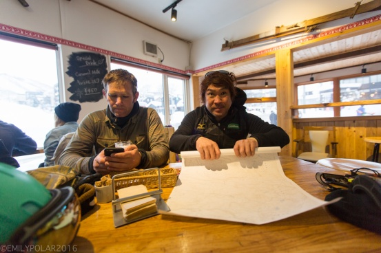 Japanese guide rolling up map of Niseko snowboarding backcountry at a cafe in Hirafu, Japan.