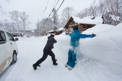Boys having a snowball fight while waiting for the van to go snowboarding in Niseko, Japan.