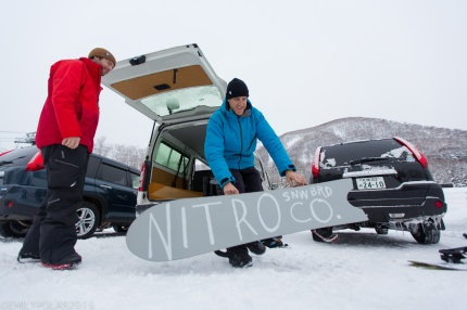 Boys unloading the snowboards from the van at Niseko Higashiyama Resort in Niseko, Japan.
