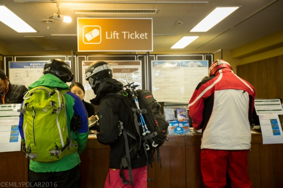 Snowboarder buying a day pass at Niseko Higashiyama resort in Niseko, Japan.