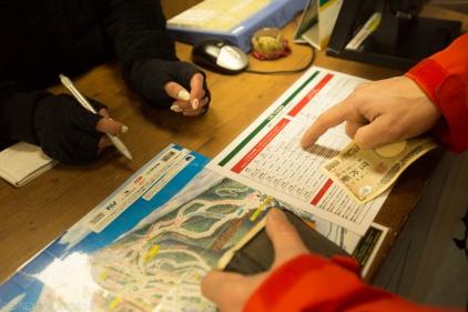 Snowboarder buying a day pass at Niseko Higashiyama resort in Niseko, Japan.