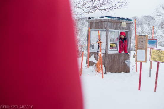 Japanese man working at a saftey check before going out of bounds at niseko higashiyama resort in Niseko, Japan.