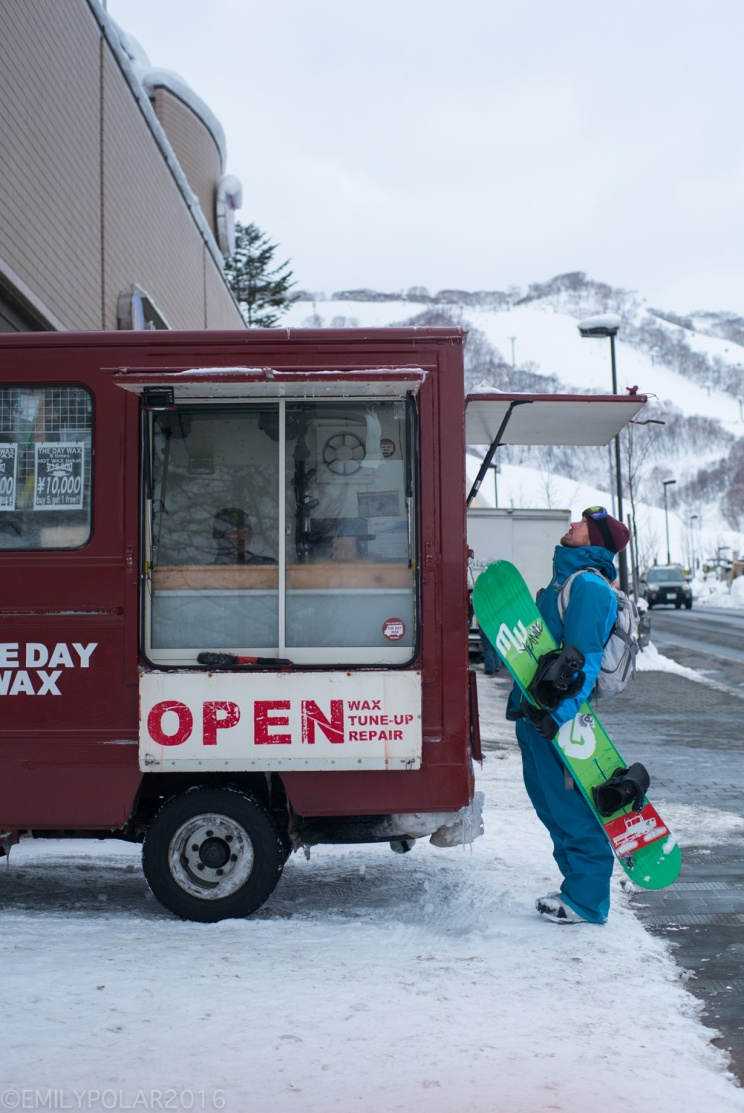 Snowboarder checking out wax and tuning truck parked near the base of Hirafu in Niseko, Japan.