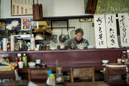 Old Japanese woman prepares ramen in her small home restaurant in Rankoshi, Hokkaido, Japan.