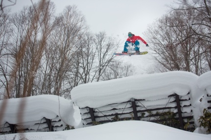 Snowboarder jumping off of avalanche barriers in Niseko, Japan.