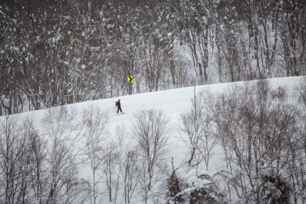 Skiers and snowboarders move along the snowy road after riding some road side powder in Niseko, Japan.