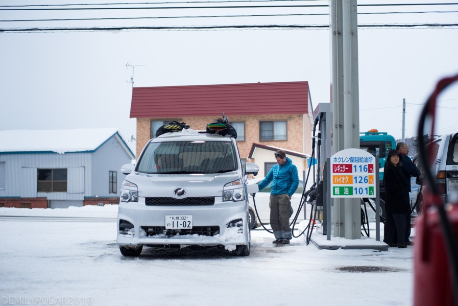 Man filling up the Japan van with gas at a snowy petrol station in Hokkaido.