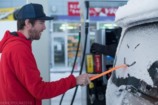 Man making smiley face in the snow with scraper on rear window of van in Japan.