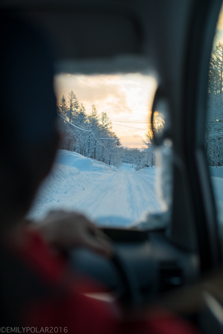 View of a snowy road from the backseat of the van in Japan.